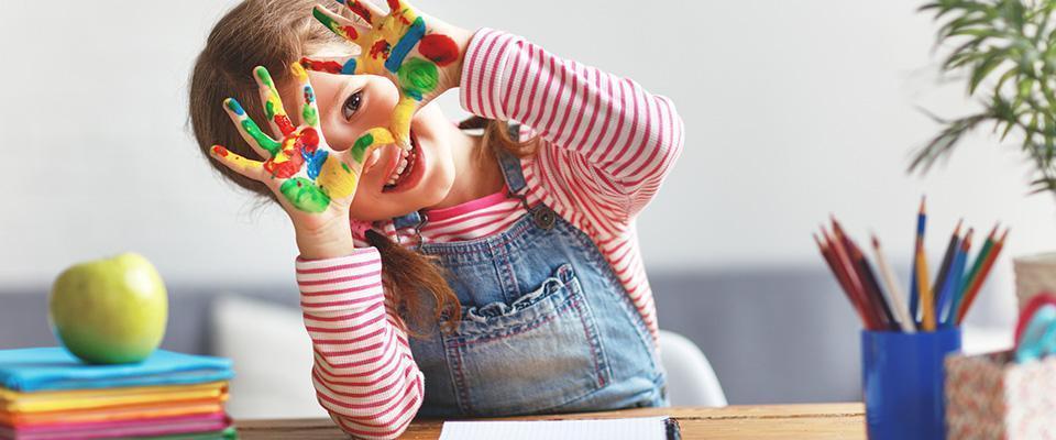 Dziewczynka zpomalowanymi farbami dłońmi